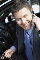 Businessman using mobile phone in car smiling half-length