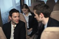 Businessmen talking to each other  businesswoman using laptop
