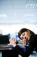 Businesswoman sleeping with her head on a stack of books