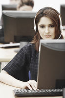 Close-up of a businesswoman wearing a headset sitting in front of a computer