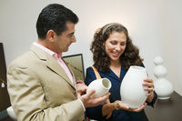 Couple examining vases in furniture shop