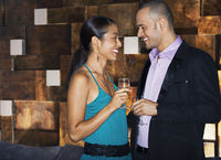 Couple flirting standing face to face in bar