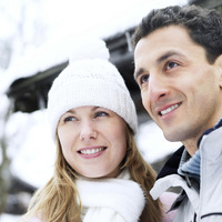 Couple in warm clothing looking away