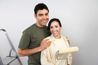 Couple standing in unpainted room with paint roller portrait