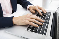 Cropped image of senior businesswoman typing on laptop