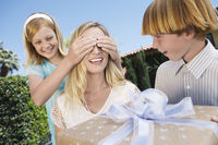 Daughter covering eyes of mother who s receiving gift from her children outside