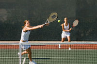 Doubles player stretching hitting tennis ball with backhand near net