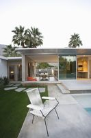 Empty chair on paved poolside area of palm springs home
