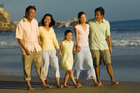 Family with girl  7-9  walking on beach