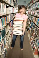Female college student in a library holding stack of books