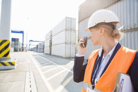 Female engineer using walkie-talkie in shipping yard