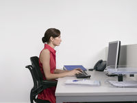 Female office worker using computer at desk in office