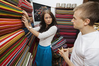 Female salesperson assisting man in textile store