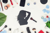Flatlay of makeup accessories and silhouette of a woman