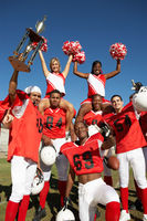 Football players and cheerleaders holding up trophy