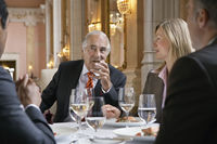 Four business people sitting at restaurant table talking