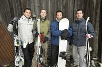 Four men in winter clothing holding snowboard