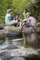Popular : Four teenagers  16-17 years  sitting on stone by river talking