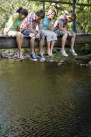 Four teenagers  16-17 years  sitting on wooden bridge looking down at stream smiling