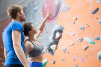 Popular : Friends discussing by climbing wall in crossfit gym