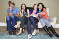 Popular : Friends sitting eating popcorn watching movie on sofa