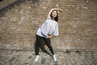 Full length of fit woman performing stretching exercise against brick wall
