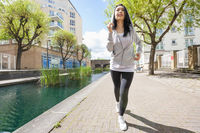 Full length of fit young woman running by canal against buildings