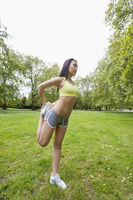 Full length of young fit woman performing stretching exercise at park