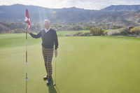 Popular : Full length portrait of happy senior male golfer holding flag and putter at golf course