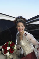 Girl  13-15  with bouquet getting out of limousine at quinceanera
