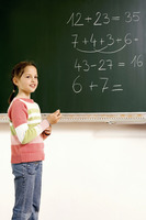 Girl holding a chalk standing near the blackboard