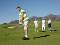 Popular : Golfer putting green friends in background