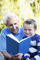 Grandfather and grandson sharing a book