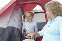 Grandmother and grand-daughter sit at entrance to tent