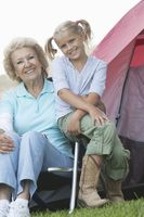 Grandmother and grand-daughter sit outside a tent