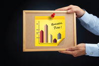 Hands holding a board with business plan bar chart