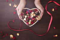 Hands presenting heart shaped bowl with dried flowers