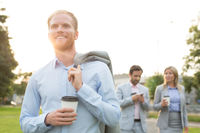 Popular : Happy businessman holding disposable cup with colleagues standing in background