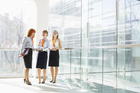 Happy businesswomen standing against glass wall in office