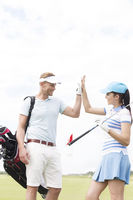 Popular : Happy male and female friends giving high-five at golf course