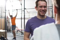 Popular : Happy man talking to male friend in crossfit gym