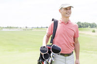 Popular : Happy middle-aged man looking away while carrying golf bag