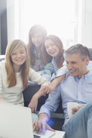Happy parents with daughters using laptop in living room