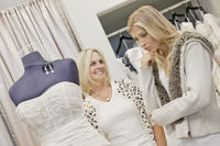 Happy senior mother looking at young daughter in bridal store