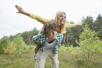 Happy woman enjoying piggyback ride on man in forest