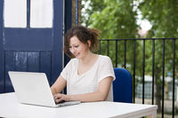 Happy young businesswoman working on laptop at desk