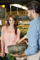 Happy young woman looking at store clerk in supermarket
