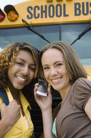 High school girls listening to cell phone by school bus