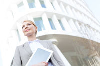 Low angle view of confident businesswoman holding digital tablet outside office building