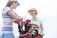 Popular : Low angle view of happy female golfers talking against clear sky